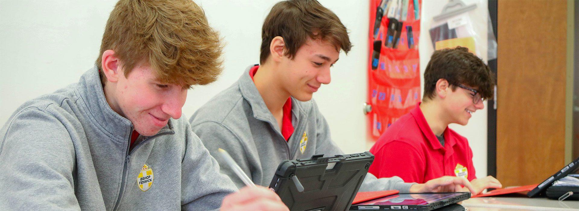 boys sitting at laptops smiling